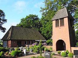 Kleine rot geklinkerte Kapelle mit freistehem Glockenturm in einer Friedhofanlage.