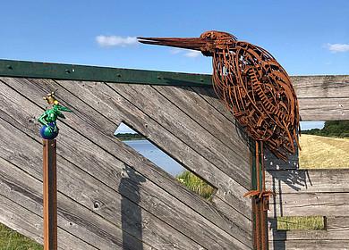 Vor einer hölzernen Wand stehen ein grüner Frosch und ein brauner Reiher aus Eisen und schauen sich an.