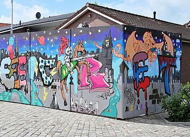 Eine mit Graffiti besprühte Holzbox steht vor der Apen Touristik