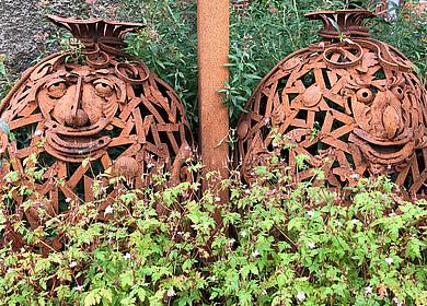 Zwei Mehlsäcke aus Eisen stehen vor einer historischen Mühle