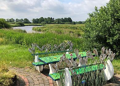 Eine verschiedenfarbige Eisenbank steht auf einem grünen Deich mit Blick auf einen Fluss