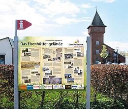 Eine Schautafel mit Informationen zur Eisenhütte. Im Hintergrund ist der Eisenhüttenturm zu erkennen.