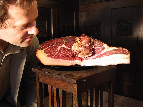 Ein angeschnittenes Stück Schweineschinken wird auf einem Tisch präsentiert. Daneben schaut ein Männergesicht sich den Schinken interessiert an.