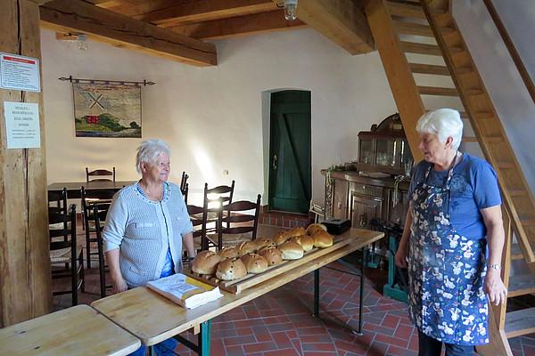 2 Frauen verkaufen frisch gebackenen Stuten auf Holztischen. Im Hintergrund ein, mit alten Möbeln eingerichteter Raum.