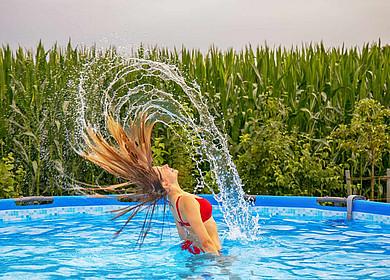 Eine Frau in einem Swimmingpool mit nassen zurückgeworfenen Haaren