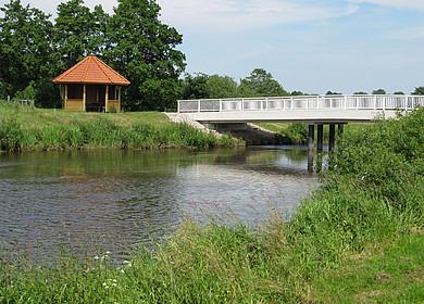 Schutzhütte am Uferrand eines Flusses. In unmittelbarer Nähe überspannt eine weiße Brücke den Fluss. Im Hintergrund ist eine grüne Landschaft mit Bäumen zu sehen.