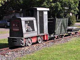 Eine Kleinbahn bestehend aus Lokomotive und 2 Anhängern steht auf einem Gleisbett in einer Grünfläche.