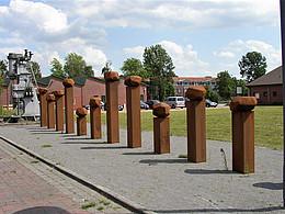 14 Eisenskulpturen in Form von viereckigen Säulen mit einer rundlichen Kugel als Abschluss und von unterschiedlicher Höhe stehen auf einem sandigen Beet. Im Hintergrund ein große Stahlpresse sowie ein öffentlicher Platz mit Häusern und Grünfläche.