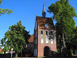 Im Vordergrund steht der prächtige Glockenturm mit vielen weiß verputzten Fensterwölbungen. Im Gibelbereicht befindet sich die Kirchenuhr. Der Himmel ist strahlend Blau. Im Hintergrund belaubter Bäume und die Kirche.