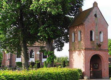 Hinter belaubten Bäumen und einer Hecke ist eine kleine Kapelle auf einer Warft zu sehen. Im Vordergrund befindet sich ein freistehender Glockentrum mit Durchlass für Besucher.