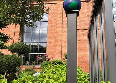 Eine kleine Weltkugel auf einer Stele steht in einem Garten vor einem historischen Gebäude