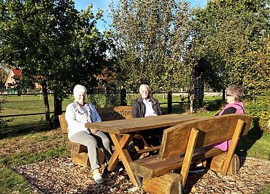 2 Frauen und 1 Mann machen Rast auf einer Bankgruppe aus Holz im strahlenden Sonnenschein.