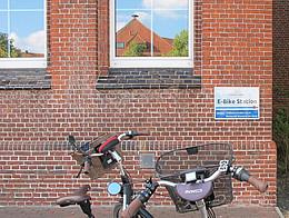 Auf einem öffentlichen Platz stehen 2 Fahrräder vor einer Ladestation für Fahrräder