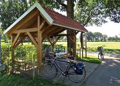 Überdachter Rastplatz mit Sitzgelegenheit und nebenstehender Informationstafel an einer Straßenkreuzung. Im Hintergrund belaubter Bäume und grüne Wiesen.