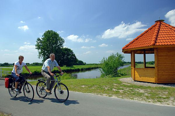 Radlerpaar unterwegs vor der Schutzhütte am Aper Tief