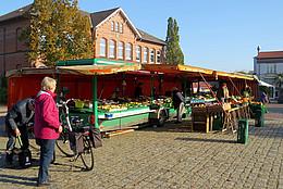 Obst und Gemüse werden auf einem Marktstand den Besuchern zum Verkauf angeboten.