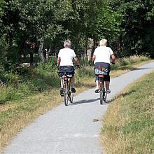 Das Foto zeigt ein 2 ältere Damen auf dem Fahrrad von hinten. Sie fahren auf einem geschotterten Fahrradweg zwischen grünen Wiesen. Im Hintergrund belaubte Bäume.