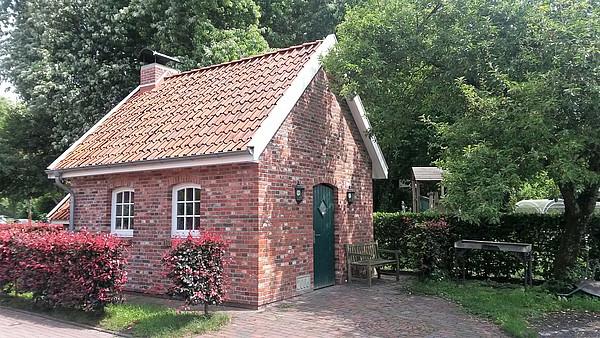 Nachbau eines kleine rot geklinkerten Backhauses nach historischem Vorbild inmitten von belaubten Hecken und Bäumen.