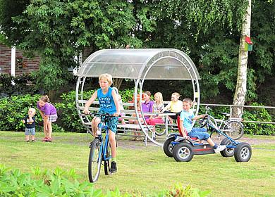Eine Kindergruppe spielt und rastet auf einer Rasenfläche. Ein Junge fährt Kettcar und ein anderer Fahrrad.