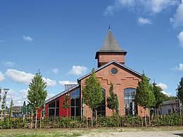 Außenansicht eines Gebäudes mit spitzem Turm in einer Grünanlage