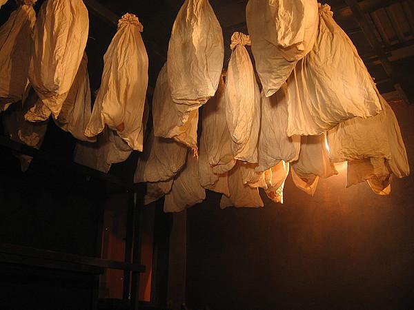 Von einer Decke mit geschwärzten Balken hängen helle Stoffbeutel herab, in denen sich geräuchterte Schinken befinden.