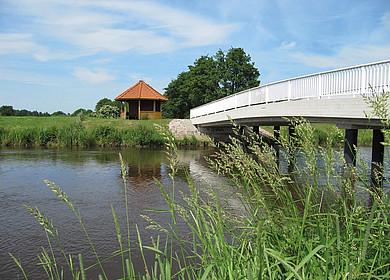 Eine weiße Brücke überspannt einen Fluss. Im Hintergrund steht eine Schutzhütte aus Holz mit rotem Dach