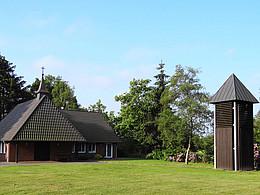 Kleine Kapelle mit freistehendem Glockenturm aus dunklem Holz in einer Grünfläche.