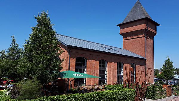 Das Bild zeigt eine Außenansicht des alten Eisenhüttenturm mit einer Eisenskulptur vor dem Terrassenbereich in Apen-Augustfehn