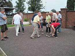 Mehrer Frauen und Männer spielen Boule auf einem Platz neben einer Mauer. Eine Frau in gebeugter Haltung hat zwei Kugeln in der Hand.