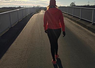 Eine Frau joggt auf einer Brücke mit Sonne von vorne
