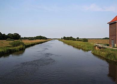 Das Bild zeigt einen Fluss mit leichter Wellenbewegung. Im Hintergrund Wiesen und belaubte Bäume. Auf der rechten Flusseite befindet sich ein Pumphaus.