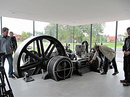 Das Bild zeigt einen verglasten Schauraum mit einer historischen Maschine mit Radantrieb. Daneben befinden sich Personen.