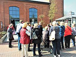 Eine Gästegruppe steht vor der Eisenhütte und hört einem Gästeführer zu