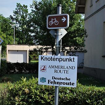 Das Foto zeigt ein Hinweisschild, das sich an diesem Ort zwei große Radrouten kreuzen.