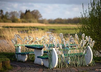 Kunsthandwerklliche Bank aus Stahl. Im Hintergrund eine Flusslandschaft