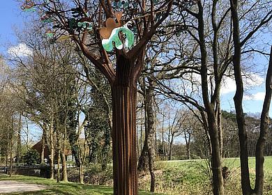 Auf einer Grünfläche steht ein nachgebildeter Baum aus Eisen