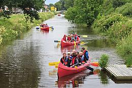 Mehrere Paddelboote auf einem Kanal mit Paddlern in Schwimmwesten legen ab vom Ufersteg. Der Kanal ist eingefasst von grüner Uferböschung.