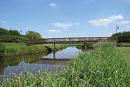 Eine schmale Holzbrücke überspannt einen Fluss