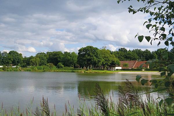 Ein See mit Strand und Haus im Hintergund, umgeben von belaubten Bäumen und grünen Wiesen