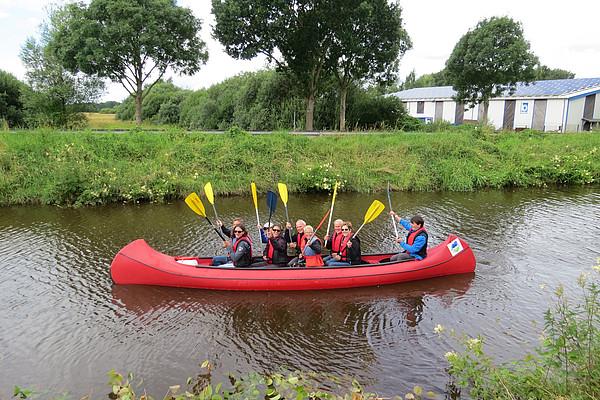 Paddlergruppe im Boot auf dem Augustfehn Kanal heben ihre Paddel zum Gruß