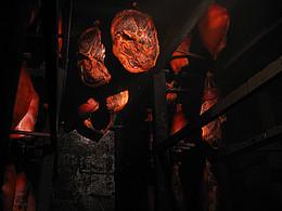 Von einer dunkel geschwärzten Decke hängen mehrere Schweineschinken herab. Im Hintergrund ist eine graue Steinwand zu sehen.