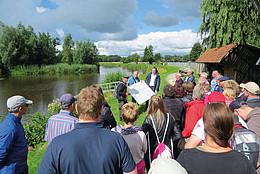 Einen Menschengruppe steht an einem Fluss mit belaubtem Hintergrund. Ein Mann hält eine Karte zur Erklärung für die Gäste